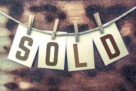 selling service: The word SOLD stamped on cards and pinned to an old piece of twine over a rusted metal background.