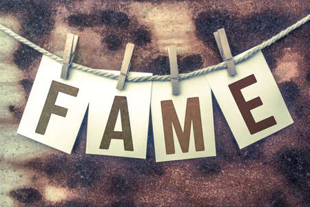 stardom: The word FAME stamped on cards and pinned to an old piece of twine over a rusted metal background.