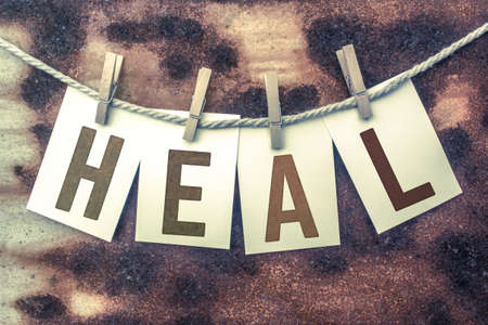 The word HEAL stamped on cards and pinned to an old piece of twine over a rusted metal background.