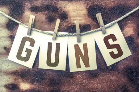 muzzleloader: The word GUNS stamped on cards and pinned to an old piece of twine over a rusted metal background.