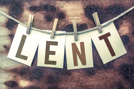 atonement: The word LENT stamped on cards and pinned to an old piece of twine over a rusted metal background. Stock Photo