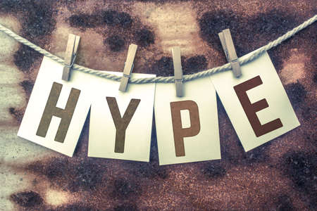 hype: The word HYPE stamped on cards and pinned to an old piece of twine over a rusted metal background. Stock Photo