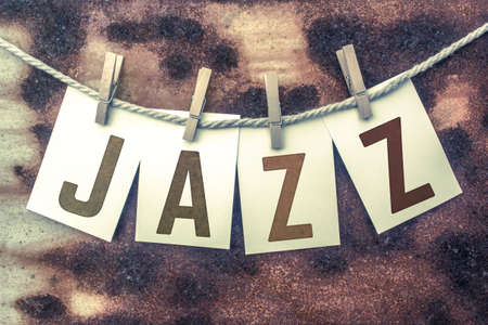 jive: The word JAZZ stamped on cards and pinned to an old piece of twine over a rusted metal background.