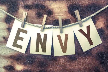 """ego�sta: La palabra """"ENVIDIA"""" estampado en las tarjetas y clavado en un viejo pedazo de hilo sobre un fondo de metal oxidado."""