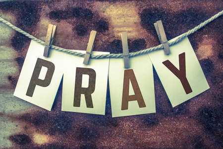 clothes pins: The word PRAY stamped on card stock hanging from old twine and clothes pins over a rusty vintage background.