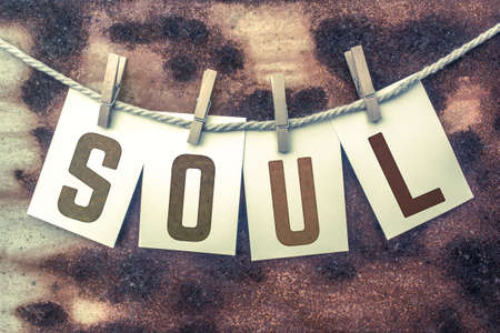 soulful: The word SOUL stamped on cards and pinned to an old piece of twine over a rusted metal background.