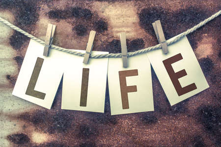 organ donation: The word LIFE stamped on cards and pinned to an old piece of twine over a rusted metal background.