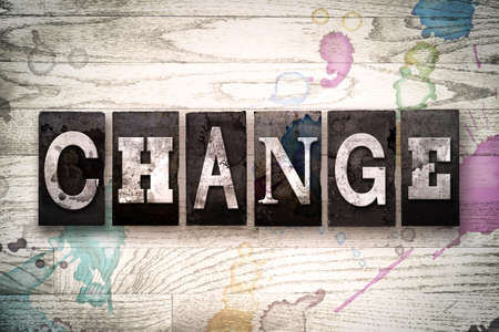 The word CHANGE written in vintage, dirty metal letterpress type on a whitewashed wooden background with ink and paint stains.