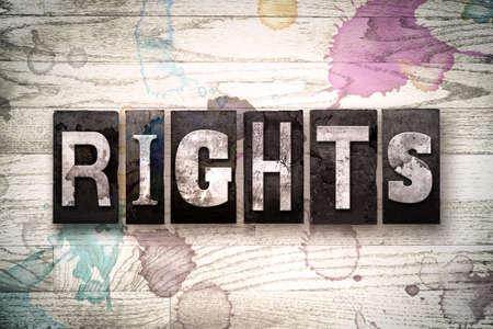 bill of rights: The word RIGHTS written in vintage, dirty metal letterpress type on a whitewashed wooden background with ink and paint stains.