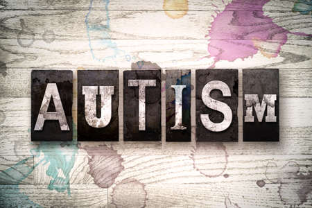 developmental disorder: The word AUTISM written in vintage, dirty metal letterpress type on a whitewashed wooden background with ink and paint stains.