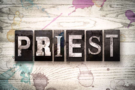 The word PRIEST written in vintage, dirty metal letterpress type on a whitewashed wooden background with ink and paint stains.