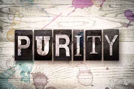 whitewashed: The word PURITY written in vintage, dirty metal letterpress type on a whitewashed wooden background with ink and paint stains. Stock Photo