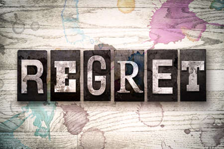 repentance: The word REGRET written in vintage, dirty metal letterpress type on a whitewashed wooden background with ink and paint stains. Stock Photo