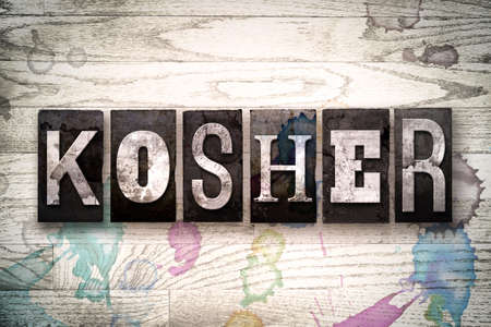whitewashed: The word KOSHER written in vintage, dirty metal letterpress type on a whitewashed wooden background with ink and paint stains.