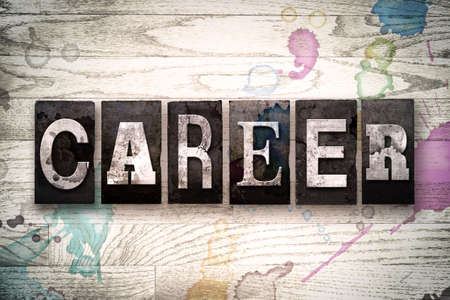 The word CAREER written in vintage, dirty metal letterpress type on a whitewashed wooden background with ink and paint stains.