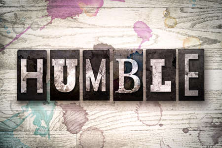 humbled: The word HUMBLE written in vintage, dirty metal letterpress type on a whitewashed wooden background with ink and paint stains. Stock Photo