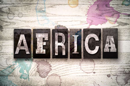 The word AFRICA written in vintage, dirty metal letterpress type on a whitewashed wooden background with ink and paint stains.