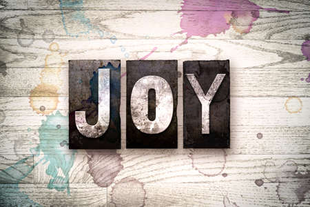gleeful: The word JOY written in vintage, dirty metal letterpress type on a whitewashed wooden background with ink and paint stains. Stock Photo