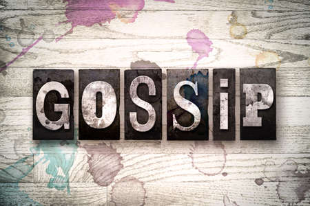 hearsay: The word GOSSIP written in vintage, dirty metal letterpress type on a whitewashed wooden background with ink and paint stains. Stock Photo
