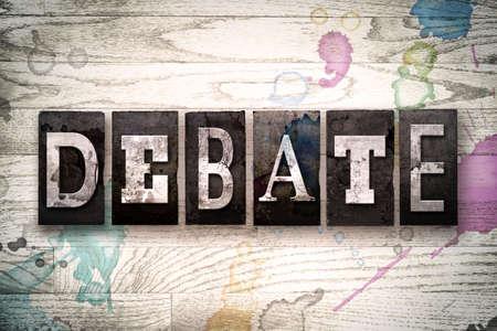 Het woord 'debat' geschreven in vintage, vuile metalen boekdruk letters op een witte houten achtergrond met inkt en verf vlekken.