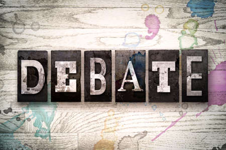 The word DEBATE written in vintage, dirty metal letterpress type on a whitewashed wooden background with ink and paint stains.