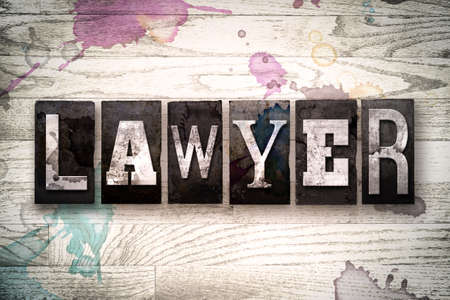 The word LAWYER written in vintage, dirty metal letterpress type on a whitewashed wooden background with ink and paint stains.