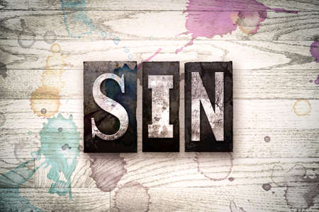 damnation: The word SIN written in vintage, dirty metal letterpress type on a whitewashed wooden background with ink and paint stains. Stock Photo