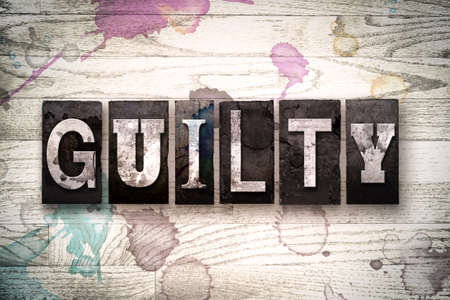 The word GUILTY written in vintage, dirty metal letterpress type on a whitewashed wooden background with ink and paint stains. Stock Photo