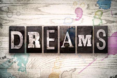 """Het woord """"Dromen"""" geschreven in vintage, vuile metalen boekdruk letters op een witte houten achtergrond met inkt en verf vlekken."""