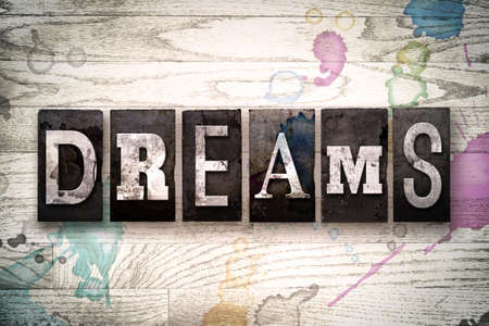 The word DREAMS written in vintage, dirty metal letterpress type on a whitewashed wooden background with ink and paint stains. Stock Photo