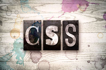 css: The word CSS written in vintage, dirty metal letterpress type on a whitewashed wooden background with ink and paint stains.
