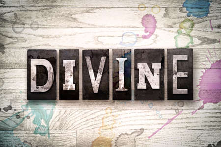 The word DIVINE written in vintage, dirty metal letterpress type on a whitewashed wooden background with ink and paint stains.