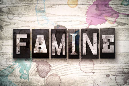 famine: The word FAMINE written in vintage, dirty metal letterpress type on a whitewashed wooden background with ink and paint stains. Stock Photo