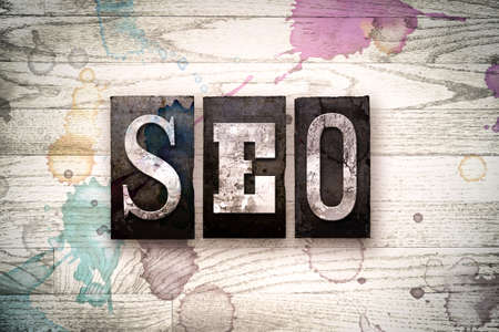 The word SEO written in vintage, dirty metal letterpress type on a whitewashed wooden background with ink and paint stains. Stock Photo
