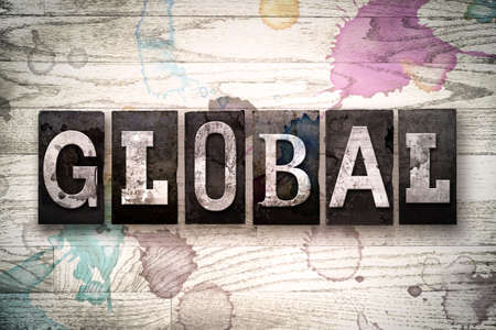 The word GLOBAL written in vintage, dirty metal letterpress type on a whitewashed wooden background with ink and paint stains.