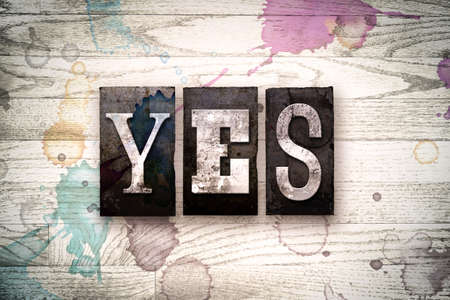 validation: The word YES written in vintage, dirty metal letterpress type on a whitewashed wooden background with ink and paint stains.