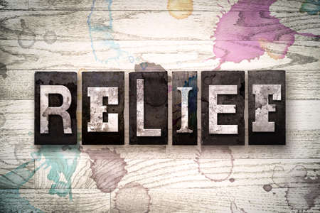 respite: The word RELIEF written in vintage, dirty metal letterpress type on a whitewashed wooden background with ink and paint stains. Stock Photo