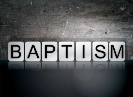 The word Baptism written in white tiles against a dark vintage grunge background. Stock Photo