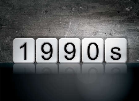 decade: The word 1990s written in white tiles against a dark vintage grunge background. Stock Photo