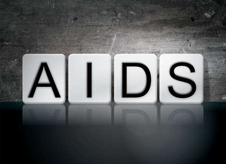 The word AIDS written in white tiles against a dark vintage grunge background. Stock Photo