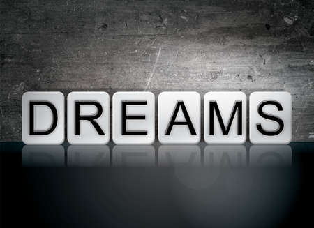 The word Dreams written in white tiles against a dark vintage grunge background.