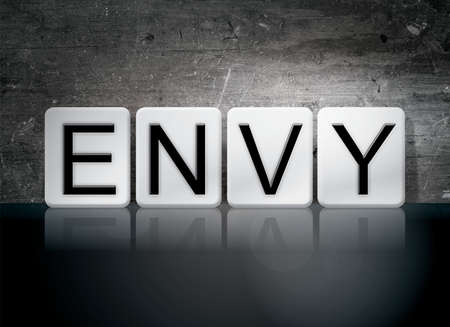 crave: The word Envy written in white tiles against a dark vintage grunge background.