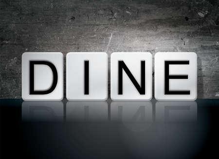 """Het woord """"Dineren"""" geschreven in witte tegels tegen een donkere vintage grunge achtergrond."""