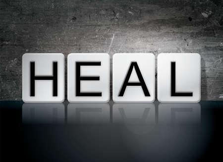 The word Heal written in white tiles against a dark vintage grunge background. Stock fotó