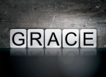 clemency: The word Grace written in white tiles against a dark vintage grunge background. Stock Photo