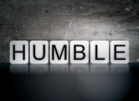 The word Humble written in white tiles against a dark vintage grunge background.