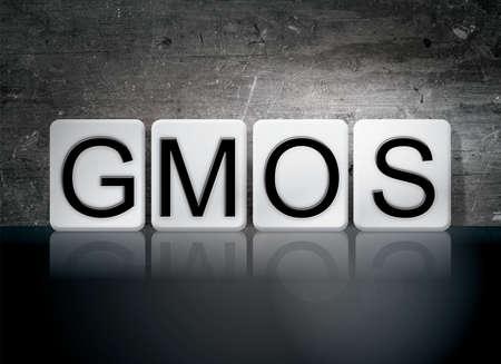 manipulated : alter: The word GMOs written in white tiles against a dark vintage grunge background.