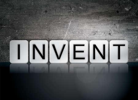 """Het woord """"uitvinden"""" geschreven in witte tegels tegen een donkere vintage grungeachtergrond. Stockfoto"""