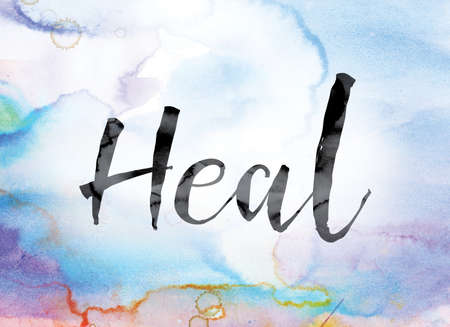 soothe: The word Heal painted in black ink over a colorful watercolor washed background concept and theme. Stock Photo