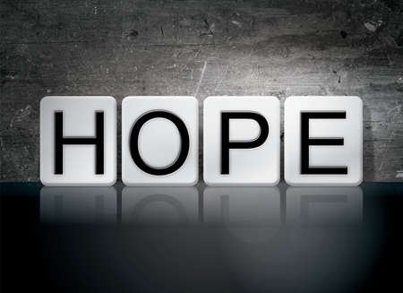 The word Hope written in white tiles against a dark vintage grunge background. Stock Photo